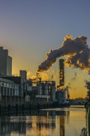 impurity: vertical photo of a factory with pipes and smoke in evening light
