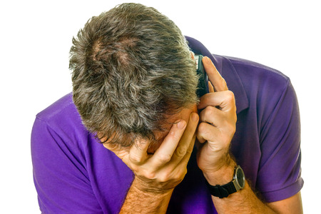 Man covering eyes in distress while on the phone   photo