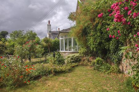 Cottage with rose garden in a British Village Stock Photo