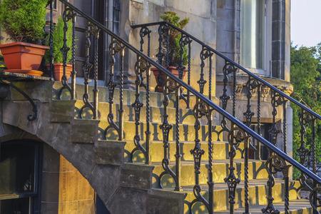 鉄の手すり、玄関、古典的な手すりとサイドパネルは、日没の家の入口に設計します。 写真素材