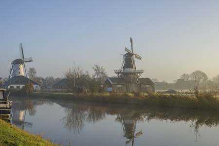 rise fall: Windmills and water in a typical Dutch countryside at sunrise with fog in Groningen