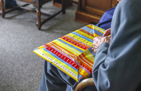 unwrapping: Old man unwrapping present at home