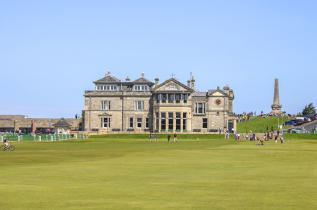 ST ANDREWS, UK-JULY 22: People walking on the old golf course at St. Andrews in Scotland in front of the famous clubhouse. The oldest course in the world is on sunday free for people to stroll.