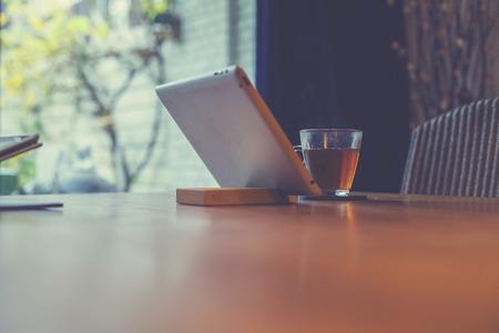 iletişim: Tablet masa üstünde evde bir bardak çay ile ayakta duruyor Stok Fotoğraf