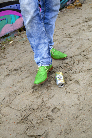 fashon: Man kicking a beer can with green shoes on sand