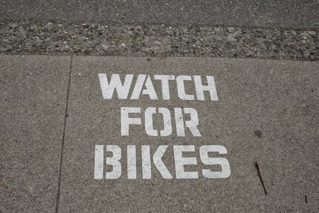 textual: Textual warning on street: watch for bikes
