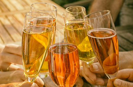 Group of friends clinking glasses of champagne with orange colors outdoors Stock Photo