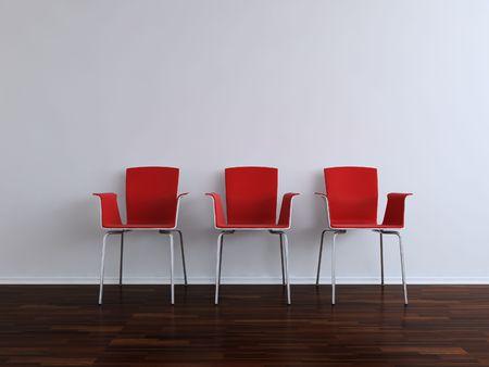 Three modern red Chais to face a blank white wall Standard-Bild