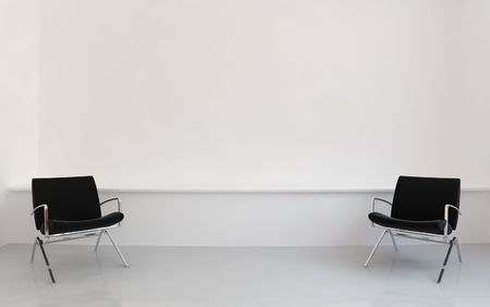 Two black Chairs to face a blank white wall