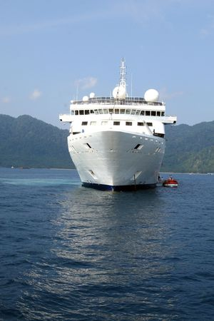 bowsprit: luxury white cruise ship with water on a clear day with calm seas.