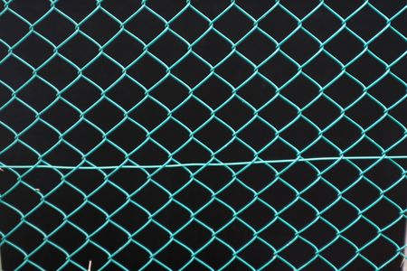 Close up shot of green wire fence against a black background. Stock Photo - 5242467