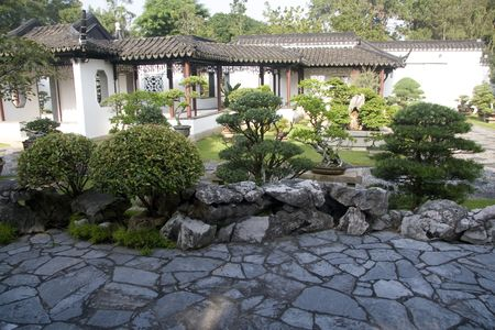 Shot of a traditional chinese style garden with bonsai, building and stone walk path. photo
