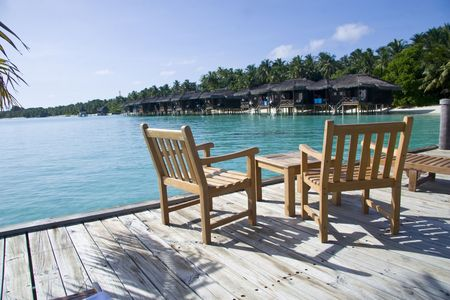 Some tables and chairs in a cafe on the beach in maldives overlooking at a row of water villa.