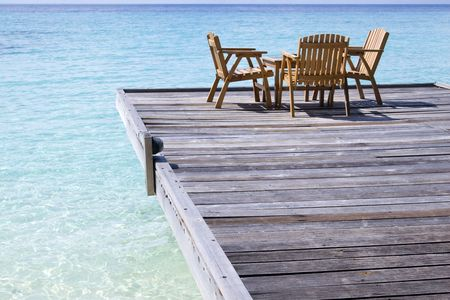 Some tables and chairs in a cafe on the beach in maldives. 版權商用圖片