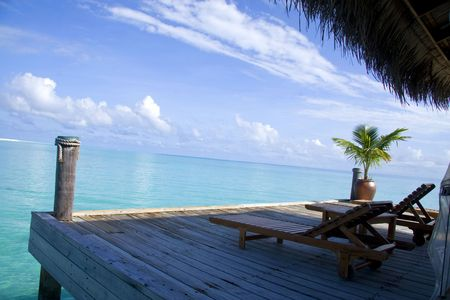 Two chairs on the balcony of a villa in maldives facing the blue sea.