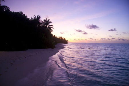 A beautiful purple sunset of the maldives seas. Showing the silhouette of island and palm trees. photo