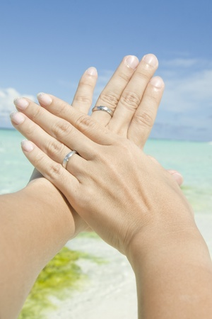 A closeup shot taken of a pair of newly weds hands with wedding rings during honeymoon. photo