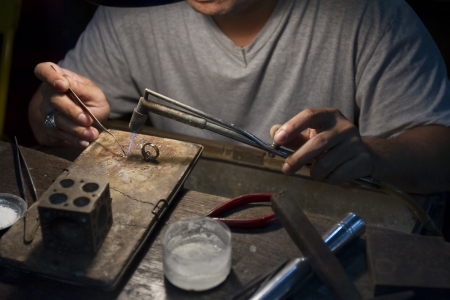 Close up shot of the making of silver rings.