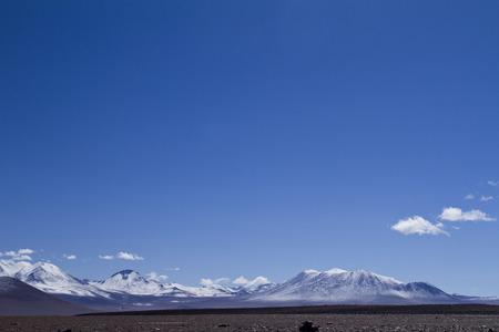 long shot: Estrema lungo colpo di gamma di montagna di neve in Uyuni, Bolivia con profondo cielo blu e copia spazio