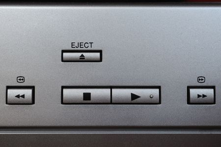 enabling: Macro photograph of play, stop, eject, rewind and fast forward buttons on a silver plated device