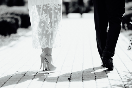 legs of the bride and groom on the pavement 免版税图像