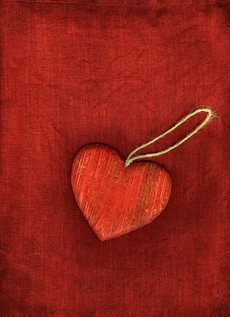 Red wooden heart with string on red background.