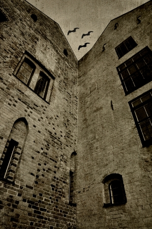 Old, scary building with bats in the sky. Textured in sepia.