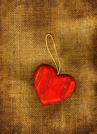 Red heart on a sackcloth in grunge. photo