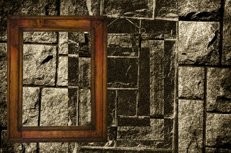 Old wooden frame in front of an old black and white stonewall. Stock Photo - 11621390