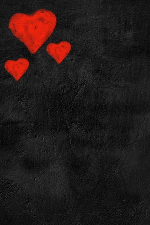 Three red hearts on black background photo