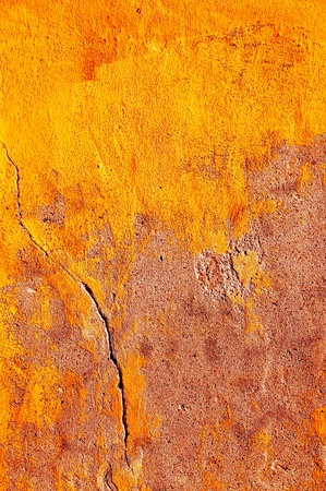 Rough wall with cracks in yellow.