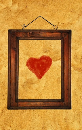 A red heart in an old wooden frame on an old rough wall. photo