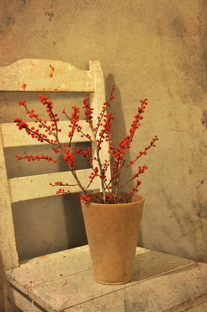 Pot with red berries on a chair, vintage look. Stock Photo