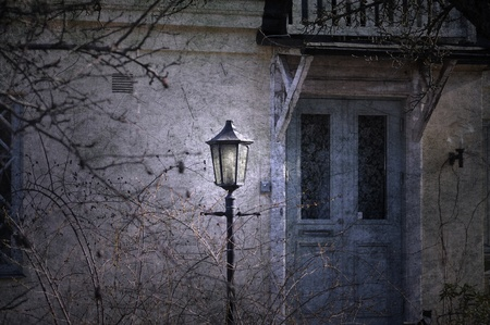 Vintage lamppost in front of a dilapidated old house with a blue door.