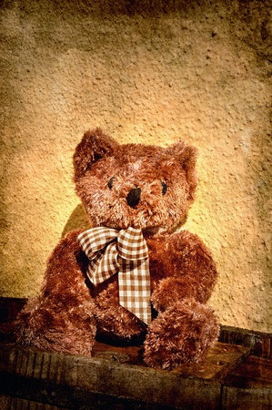 Teddy bear sitting on an old bucket in grunge Stock Photo - 13306608