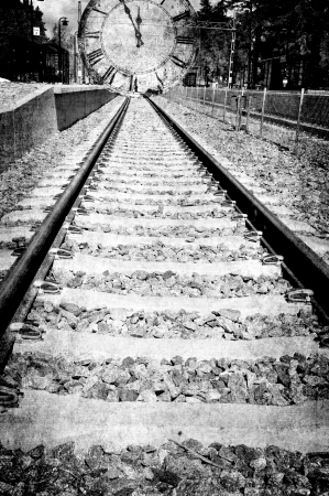 Railroad track in black and white is leading in to a clock, montage in grunge. photo