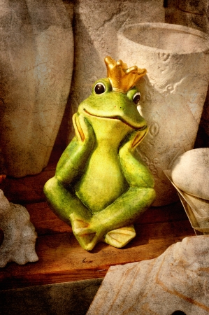 Frog prince sitting on a wooden shelf among vintage garden pots.