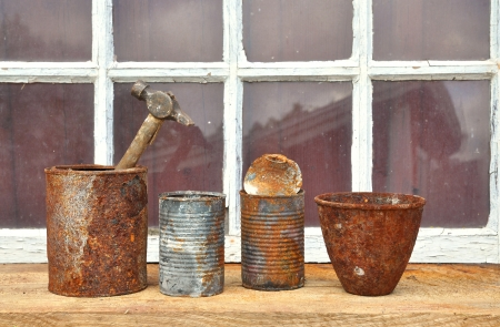 Rusty old tin cans used for tools in front of an old window. Stock Photo