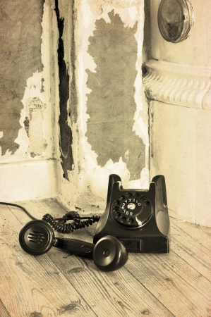 Old black bakelite phone on the floor in a grungy house with the receiver off. Stock Photo - 14166041