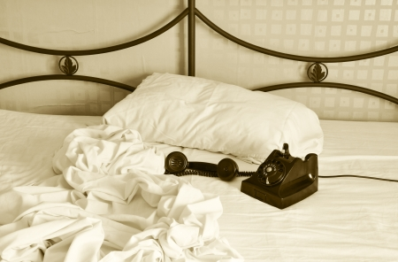 bakelite: Unmade bed with old bakelite phone with receiver off. Stock Photo