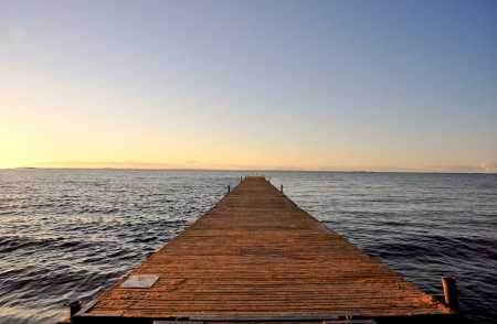 Wooden pier by the sea in sunset.