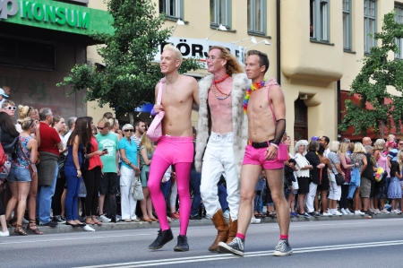 STOCKHOLM, SWEDEN - AUGUST 4: Three unidentified gay men participates in the pride parade on August 4, 2012 in Stockholm. Approximately 50,000 people march the parade and 500,000 bystanders watch.