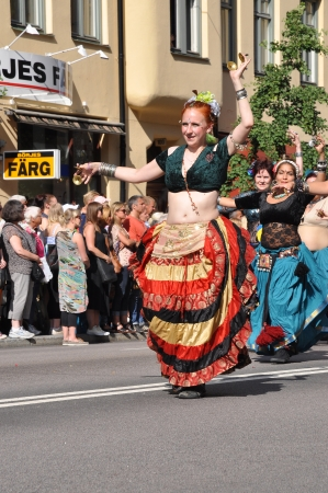 bystanders: STOCKHOLM, SWEDEN - AUGUST 4: An unidentified woman dancing belly dance in the pride parade on August 4, 2012 in Stockholm. Approximately 50,000 people march the parade and 500,000 bystanders watch the parade.