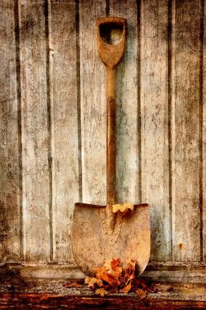 ouderwetse spade met droge bladeren tegen een oude houten muur.