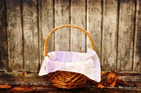 Picnic basket with autumn leaves aganst an old wooden wall.