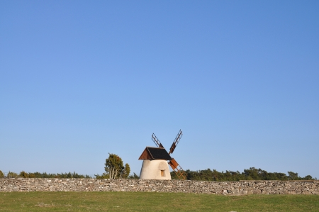 Old windmill by old stone wall in the country