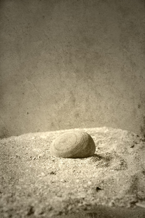 Round stone on sand in textured sepia