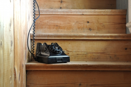 Old bakelite phone on a wooden staircase with a hidden receiver. Stock Photo
