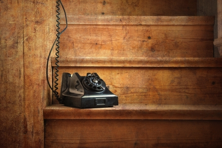 Vintage bakelite phone on a wooden staircase with a hidden receiver. Black and white image. photo