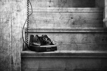 Vintage bakelite phone on a wooden staircase with a hidden receiver. Black and white image. Stock Photo - 15434645